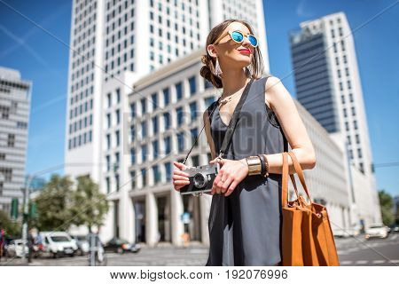 Lifestyle portrait of a businesswoman tourist walking with camera in the modern district in Frankfurt city