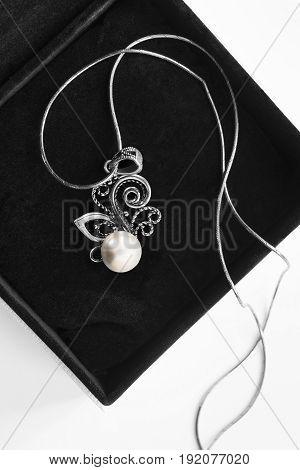 Elegant silver pearl necklace in black jewel box closeup