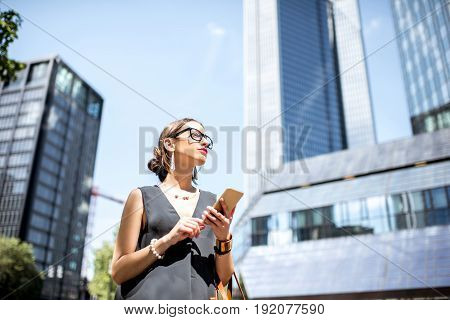Lifestyle portrait of a businesswoman with phone in the modern district in Frankfurt city