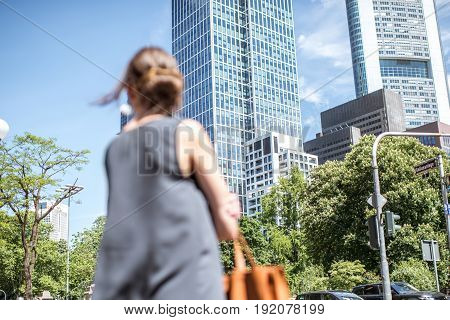 Business city with woman looking forward. Woman is not in focus