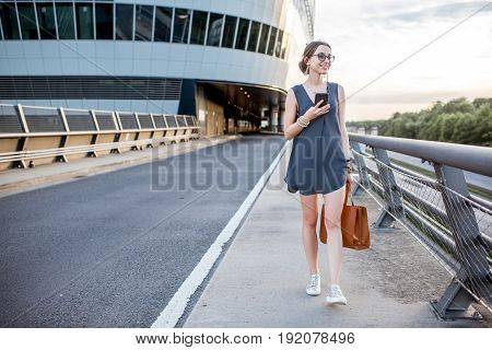 Young businesswoman walking with phone on the highway during the business trip