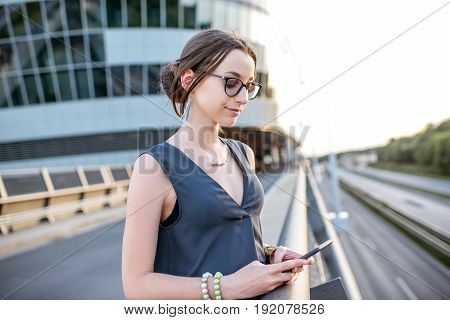 Young businesswoman standing with phone on the highway during the business trip