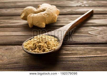 Ginger powder in wooden spoon on wooden table. Close-up. Near root of ginger