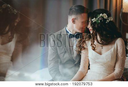 Wedding shot of stylish bride and groom sitting on bed