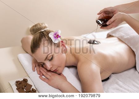 Woman lying in a beauty parlour enjoying relaxing back massage with chocolate