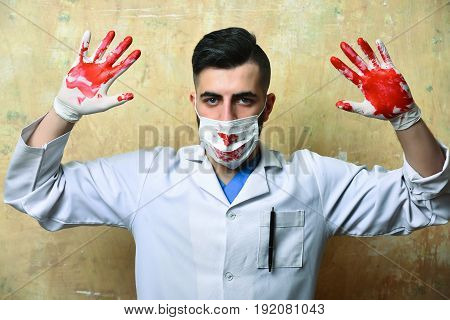 Medic In Procedure Mask With Bloody Hands Raised Up