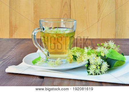 Cup of linden tea in glass mug over wooden table
