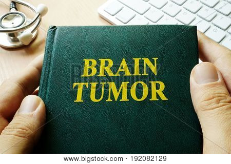 Book with title brain tumor in hands.