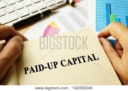 Book with title paid-up capital in an office.