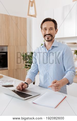 Love my work. Pleasant young bearded man standing behind the kitchen counter, holding one hand on the laptop while having a pencil in the other while looking happy