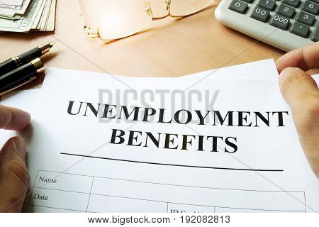 Unemployment benefits form on a table and calculator.