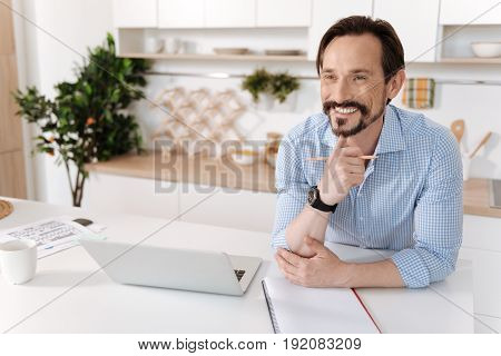 Sweet dreams. Pleasant overjoyed man sitting behind the kitchen counter with a laptop standing on it, resting his chin on the hand and looking into the distance with a broad smile