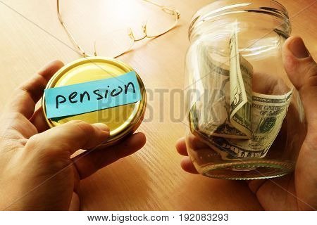 Hands holding jar with few dollars and label pension. Savings for retire.