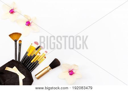 Makeup Brush In My Purse And Some Flowers Orchid On A White Background. Minimal Concept Of Beauty.
