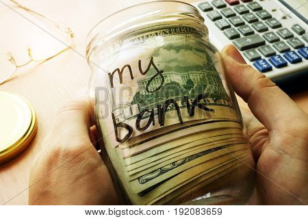 Jar with dollars and sign my bank on a side. Home finances and savings concept.