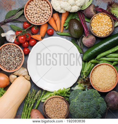 Different vegetables and grains, arranged in a circle with off white plate in the middle, broccoli, squash, beans, tomatoes, carrots, avocado, top view, square, selective focus