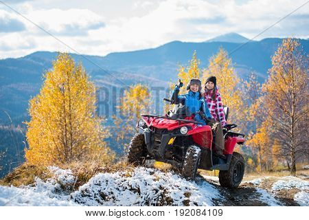 Two Women Riders Atv In Jackets And Hats On A Snow-covered Trail At Sunny Autumn Day Against Trees W