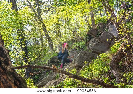 the girl rises through beautiful forested cliff, lots of greenery and cliffs. sunny day