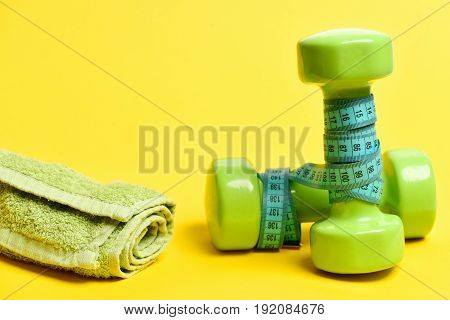 Dumbbells With Cyan Measuring Tape And Green Towel