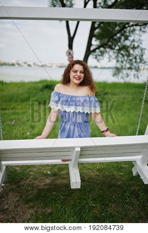 Portrait Of A Stunning Young Girl Wearing Blue Marine-styled Dress Sitting On Swings On The Lakeside