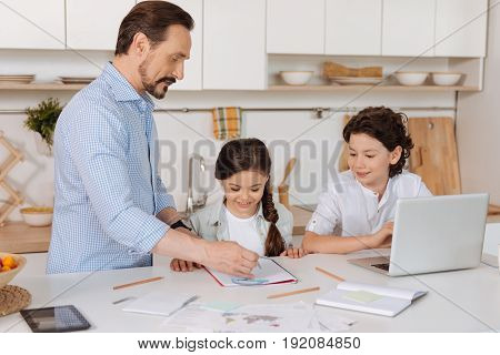 Best teacher. Handsome bearded father holding a pair of compasses and explaining a math task to his son and daughter while they listening to him attentively