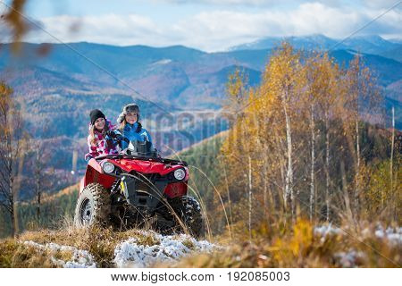 Beautiful Females Riding On Red Quad Bike In Winter Clothing On Snowy Hills On The Background Of Mig