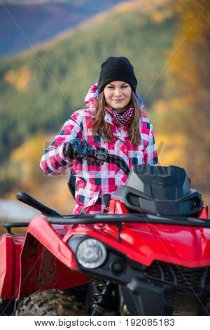 Close-up Pretty Girl In Winter Clothing On Red Quad Bike Looking At The Camera On The Blurred Backgr