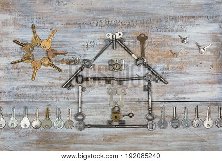 Background with a house shape with a fence and the sun made with old keys on old painted wooden boards. Top view