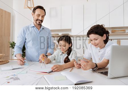 Exciting novelties. Cheerful handsome boy holding a set square while his sister using a pair of compasses and their pleasant young father looking at them with an affectionate smile