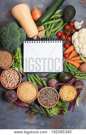 Colourful vegetables and grains, arranged in a circle with white notebook in the middle, broccoli, squash, beans, tomatoes, carrots, avocado, top view, selective focus