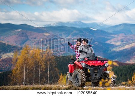 Young Couple On Red Quad Bike Ride In Mountains. Happy Man Driving The Atv, Girlfriend Pointing At S