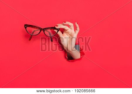 Crop hand in hole torn in red paper holding elegant glasses.
