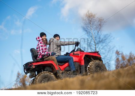 Bottom View Couple On The Red Atv Quad Bike Against Blue Sky With Blurred Background Nature. Girl Hu