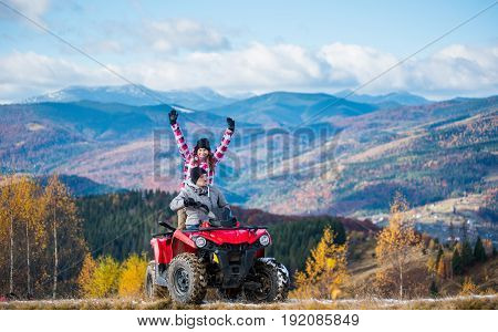 Man Driving Atv Quad Bike, Woman Sitting Behind Him And Raised Her Hands Up On A Mountain Road On A