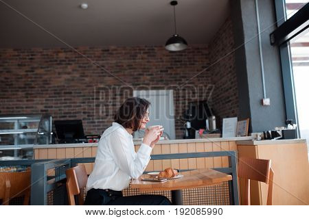 Side view of elegant woman sitting in cafe with cup of coffee and croissant.