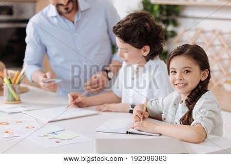 Joyful kid. Petite cute girl sitting at the kitchen counter, doing her home assignment and looking at the camera while her father and brother doing sums together in the background