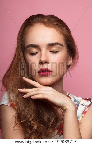 Young pretty woman with eyes closed touching chin on the pink background.