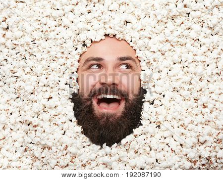 Bearded happy man lying in popcorn looking away with mouth opened.