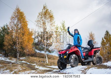 Happy Girl In Blue Winter Clothes Waving On A Red Quadbike Atv On Snow-covered Hill Against Autumn N