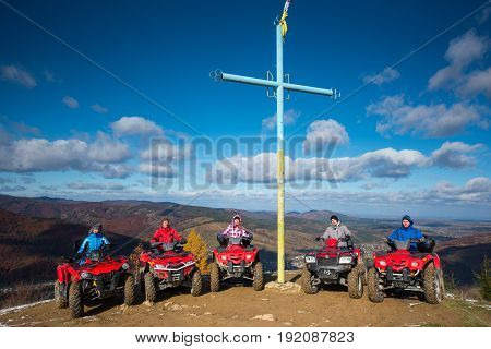Group Of People On Red Quad Bikes Near Cross With A Symbol Of Ukraine On Top Of The Mountain On The