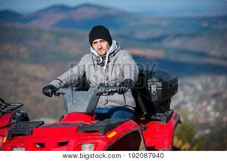Close-up Of Man In Winter Clothing On Red Quad Bike Looking At The Camera On The Blurred Background