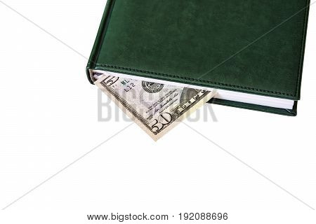 Between the sheets of the closed diary is visible part of the money bill