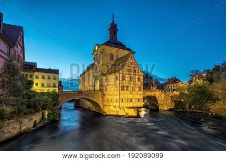 Bamberg. Illuminated building of Old Town Hall of Bamberg (Altes Rathaus) with two bridges over the Regnitz river in the evening Germany