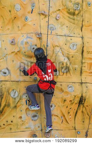 Labuan,Malaysia-May 21,2017:Muslim woman with safety equipment climb on climbing wall in Labuan,Malaysia.It is an activity in which participants climb up or across artificial rock walls
