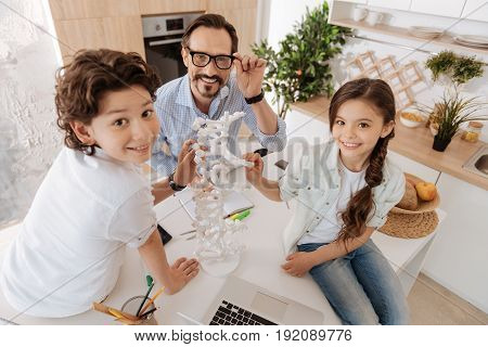 Enjoying themselves. Cute little brother and sister sitting on the kitchen counter next to their young handsome father and touching a 3D DNA model while all of them looking at the camera and smiling