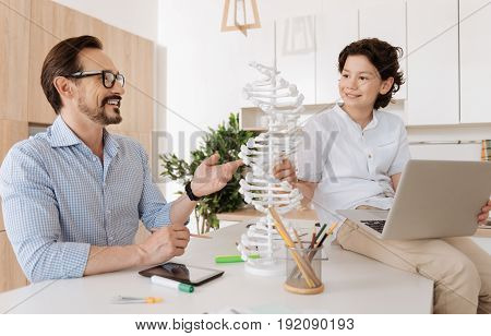 Smart talk. Handsome pleasant boy sitting on the kitchen counter with a laptop on lap and exchanging thoughts about the DNA model standing on the counter with his smiling father