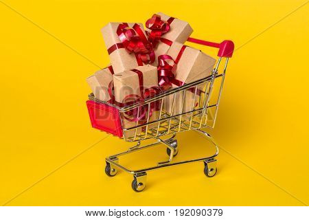 Creative concept with shopping trolley with gifts on a yellow background. Gifts wrapped in kraft paper with a red ribbon and bow.