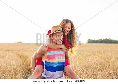 Happy Couple Having Fun Outdoors on field. Freedom Concept. Piggyback
