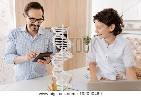 Aspiring scientist. Handsome little boy scrutinizing a big 3D DNA model while his father using a tablet to find some related information for his son