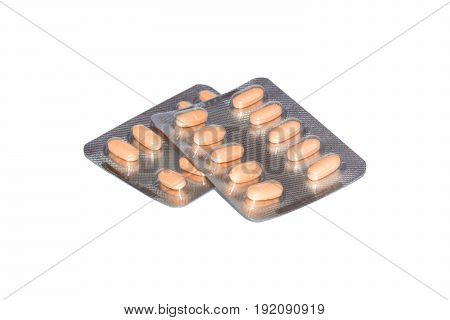 Yellow pills packed in blisters isolated on white background.